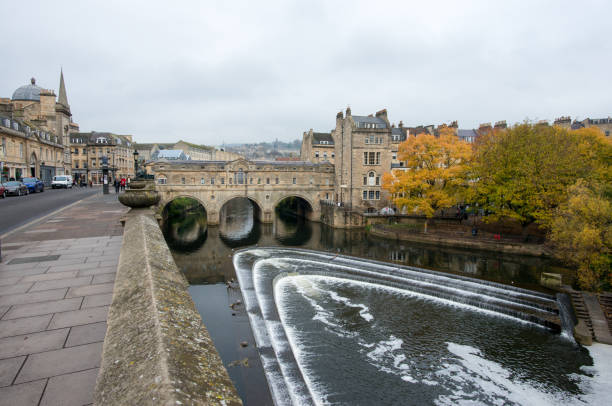 Pulteney Bridge, Bath, England Bath, England - Nov 5, 2018: The Pulteney Bridge and the water falls in autumn. roman baths england stock pictures, royalty-free photos & images