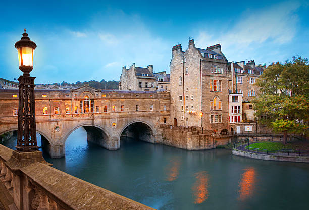 Pulteney Bridge in Bath Pulteney Bridge by dusk, the main tourist attraction in Bath, UK. somerset england stock pictures, royalty-free photos & images