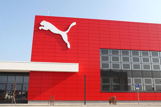 puma logo na czerwone ściany - brand name zdjęcia i obrazy z banku zdjęć