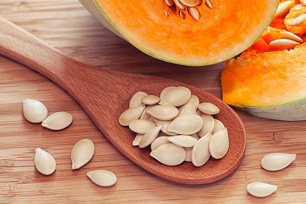 Pumkin seeds inside of wooden spoon stock photo