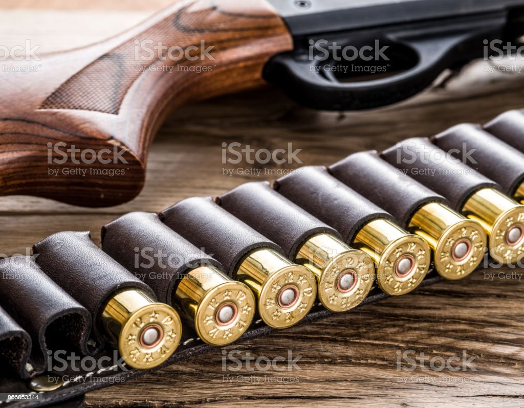 Pump action shotgun, 12 guage cartridge on the wooden table. stock photo