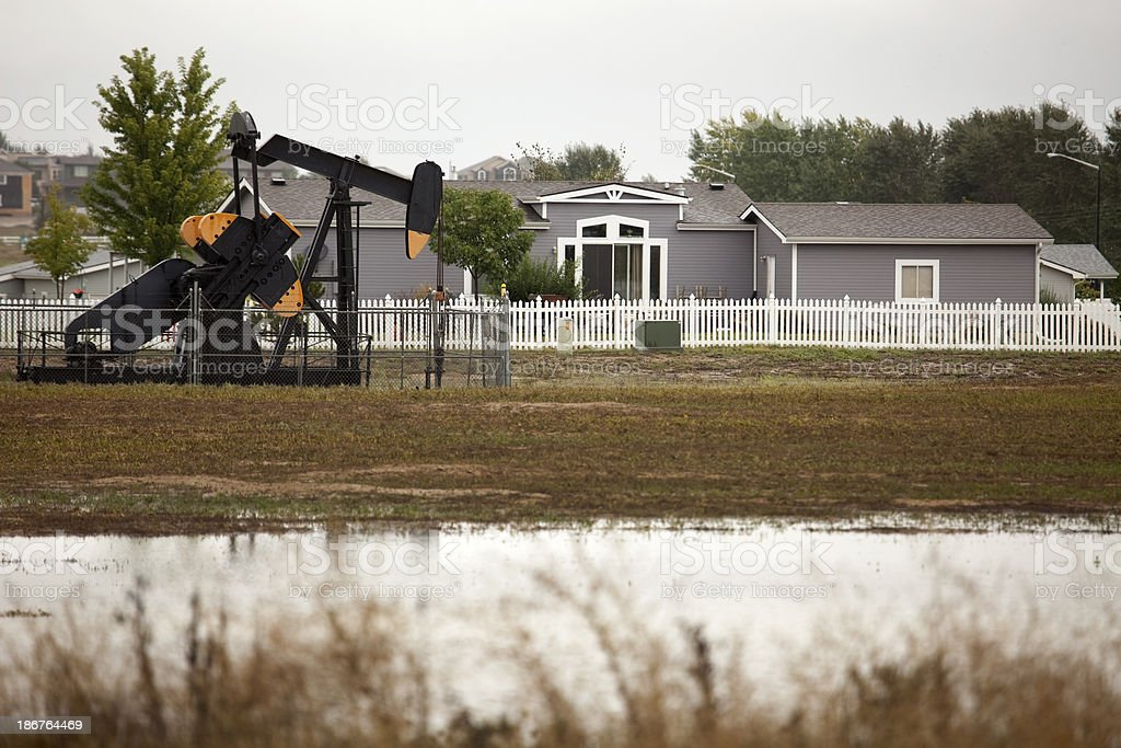 Pump jack with home and flood waters Colorado stock photo