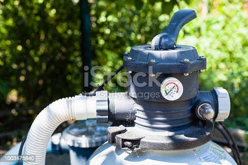 water pump of outdoor filtering system of swimming pool in summer day