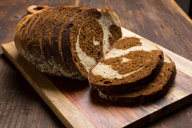 Pumpernickel and rye swirl bread Slices on cutting board stock photo
