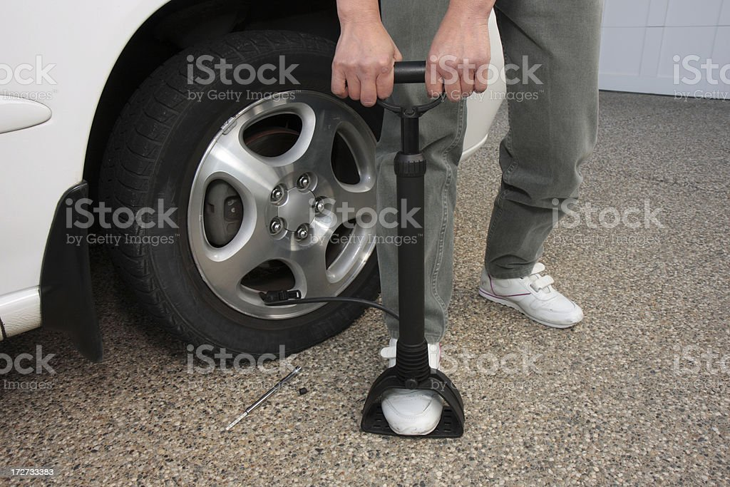 Pumping air into a car tire royalty-free stock photo
