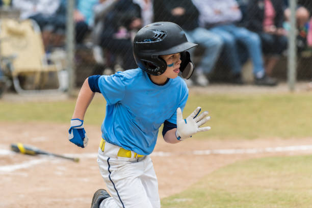 Pumping arms for extra speed for a hit. Little league batter hurrying up the first base line wearing helmet, gloves, and eye black. all star stock pictures, royalty-free photos & images