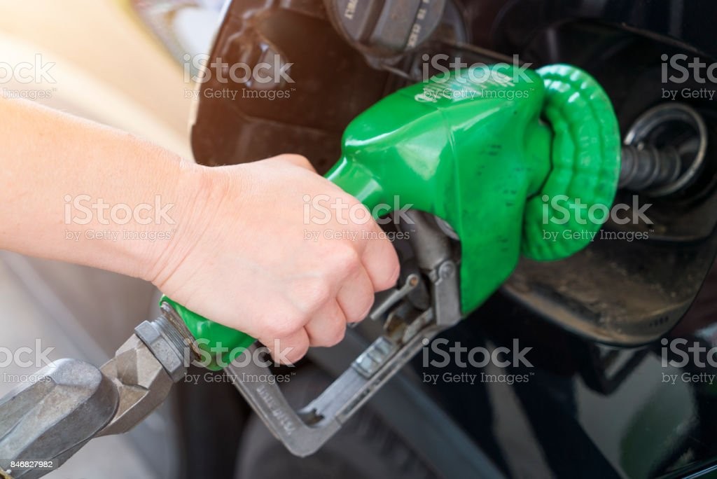 Pumping gas at USA gas station hand on nozzle stock photo