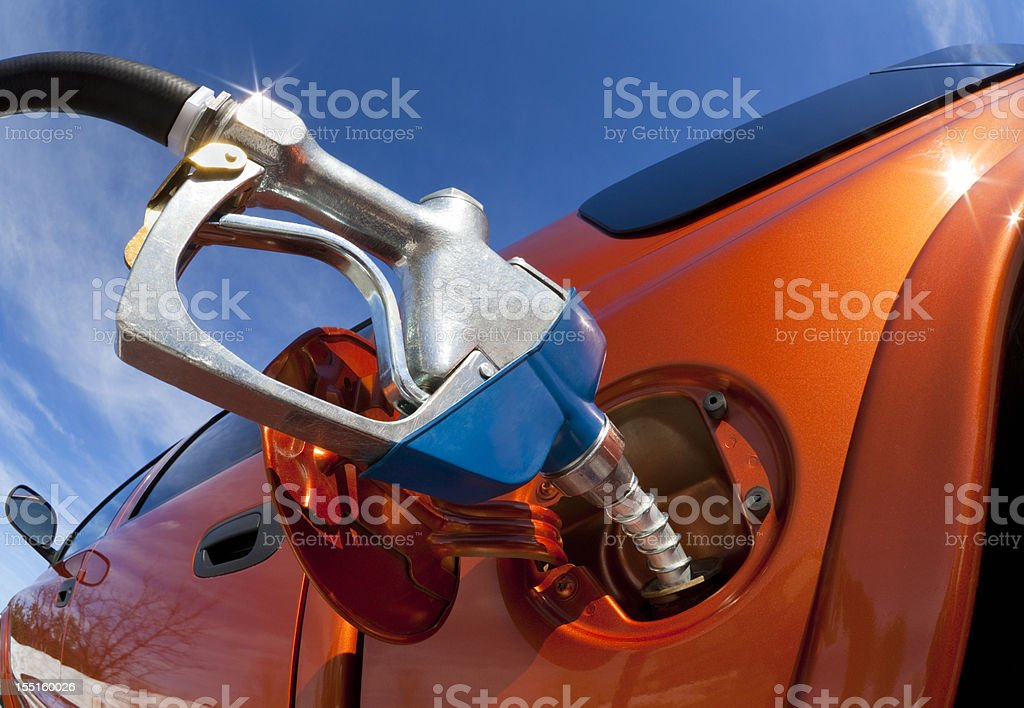 Pumping Gas Into Gas-Guzzler on a Sunny Day stock photo