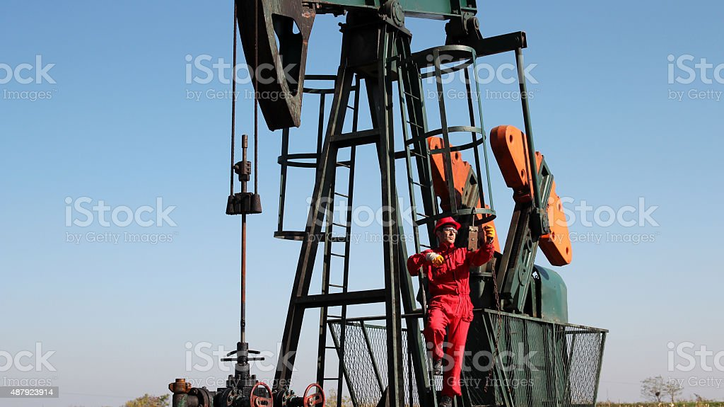 Pumpjack and Oilfield Worker Oil industry worker using chain winch on the pump jack. 2015 Stock Photo