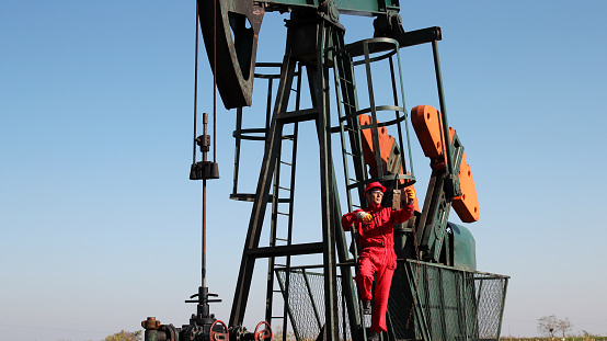 Pumpjack And Oilfield Worker Stock Photo - Download Image Now