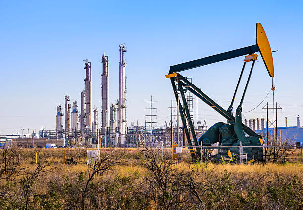 pumpjack (oil derrick) and refinery plant in west texas - crude stock pictures, royalty-free photos & images