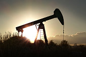 Silhouette of a pumpjack at sunset