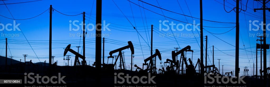 Pumpjack panoramic lifts oil from a well in California stock photo