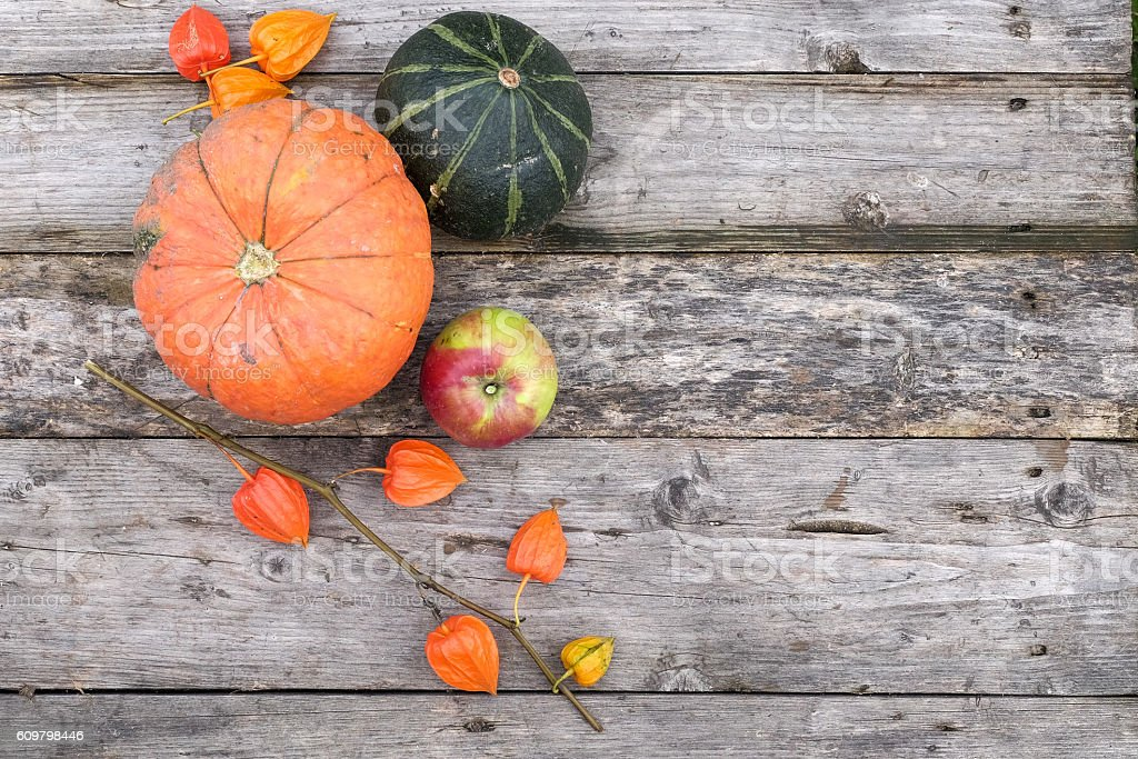 pumpkin and apple on wooden grey table stock photo