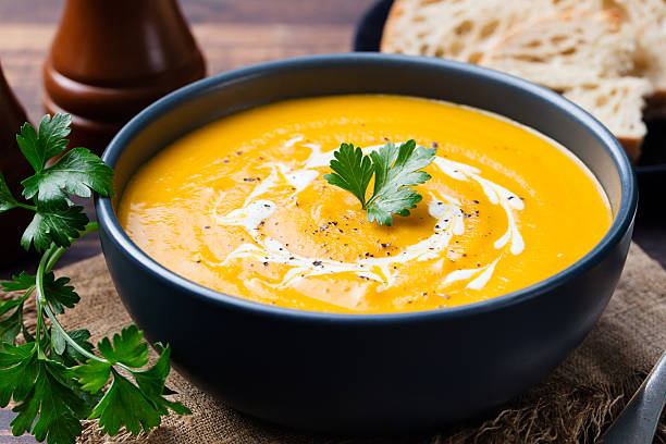 Pumpkin and carrot soup with cream and parsley Pumpkin and carrot soup with cream and parsley on dark wooden background. squash vegetable stock pictures, royalty-free photos & images