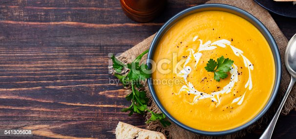 istock Pumpkin and carrot soup with cream and parsley 541305608