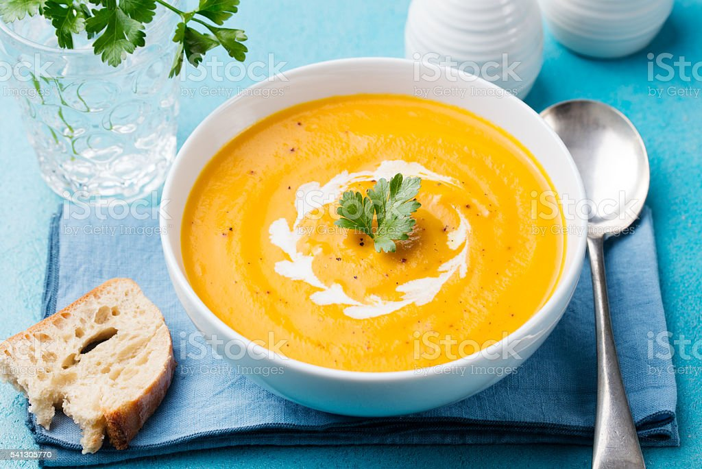 Pumpkin and carrot soup with cream and parsley stock photo