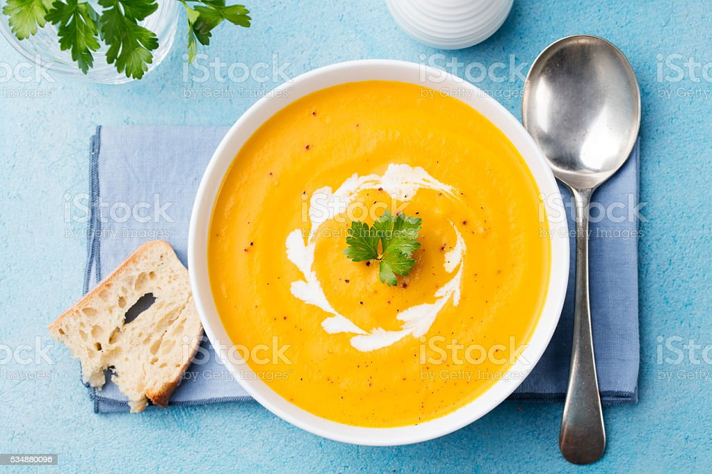 Pumpkin and carrot soup with cream and parsley Top view. stock photo