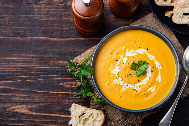 Pumpkin and carrot soup with cream and parsley Top view Pumpkin and carrot soup with cream and parsley on dark wooden background Top view Copy space curry powder stock pictures, royalty-free photos & images