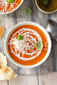 istock Pumpkin and carrot soup with cream on blue stone background. 1217347999