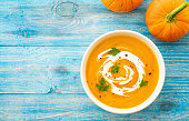 istock Pumpkin and carrot soup with parsley on blue background Top view. 1018260016