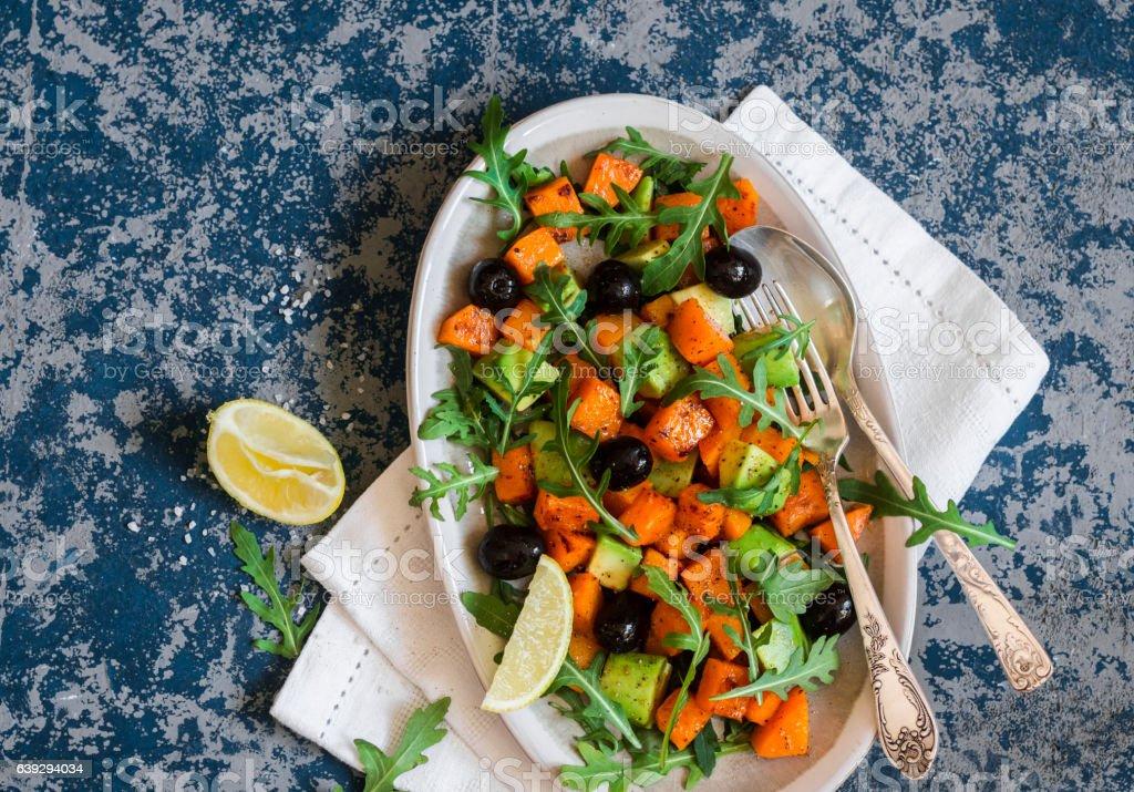 Pumpkin, avocado, olives, and arugula salad. stock photo