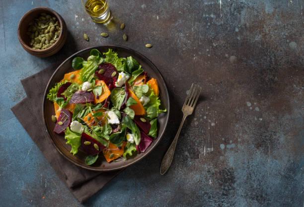 Pumpkin, beetroot, soft cheese and greens salad stock photo