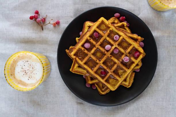 pumpkin belgian waffles with honey and viburnum and pumpkin latte. - zimt waffeln stock-fotos und bilder