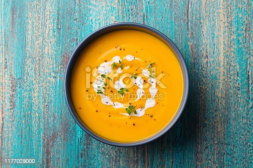 Pumpkin, carrot cream soup in a bowl. Blue wooden background. Top view
