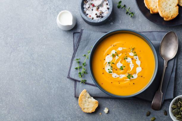 pumpkin, carrot cream soup in a bowl. grey background. top view. copy space. - sopa imagens e fotografias de stock