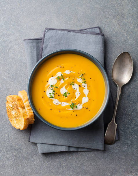 Pumpkin, carrot cream soup in a bowl. Grey background. Top view. stock photo