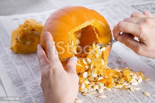Hands scooping out the seeds and pulp before carving the jack o'lantern.
