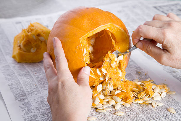 Pumpkin Carving for Halloween Hands scooping out the seeds and pulp before carving the jack o'lantern. terryfic3d stock pictures, royalty-free photos & images