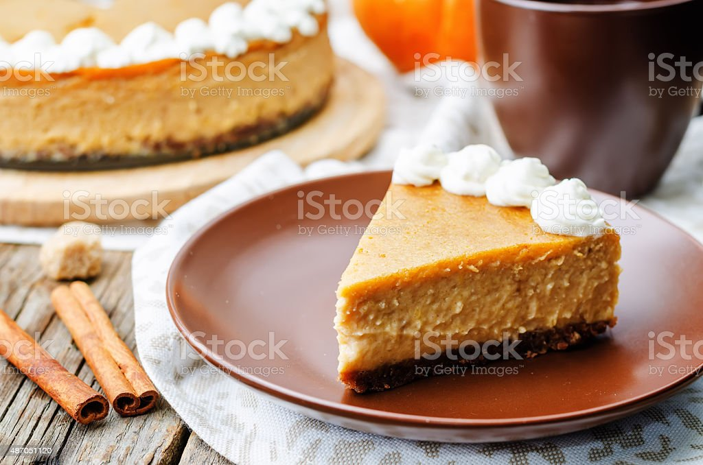 pumpkin cheesecake decorated with whipped cream stock photo