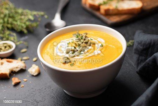 istock Pumpkin cream soup in bowl on black concrete background 1050251530