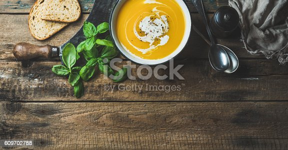 istock Pumpkin cream soup in bowl with fresh basil and spices 609702788