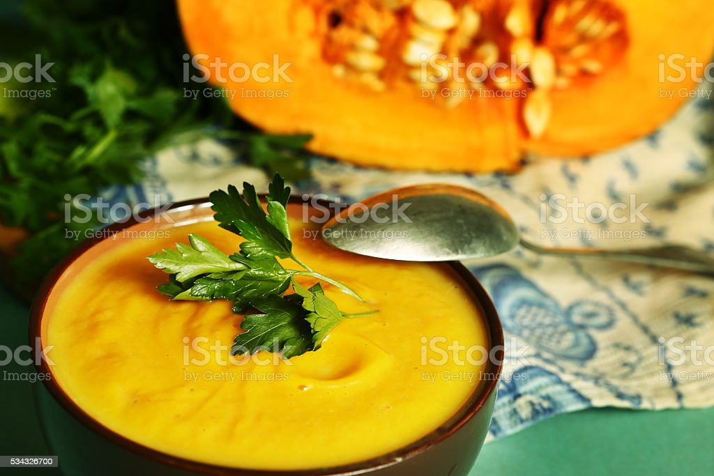 pumpkin cream soup in bowl with parsley stock photo