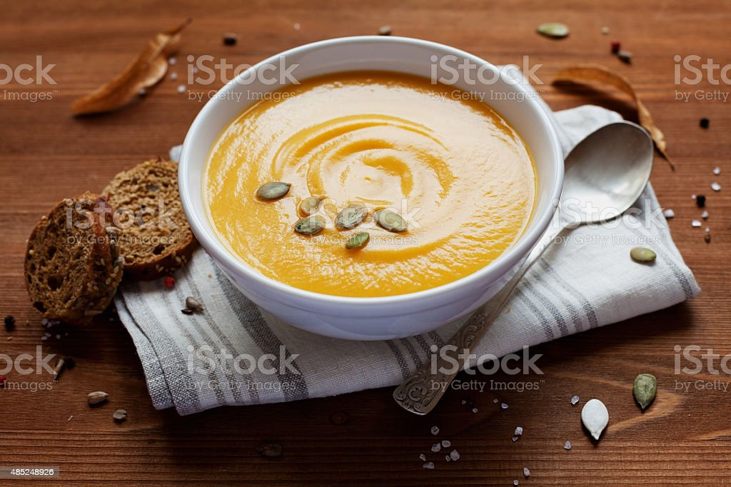 Pumpkin cream soup with bread and seeds on linen napkin stock photo