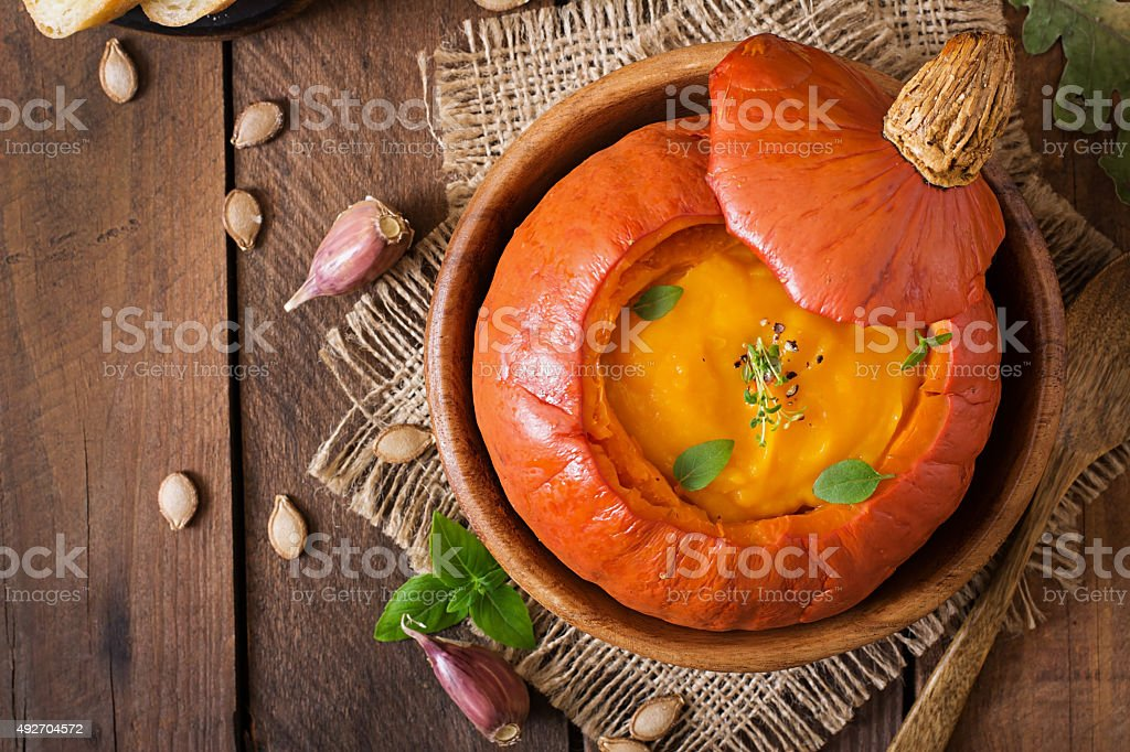 Pumpkin cream soup with peppers and herbs in a pumpkin stock photo
