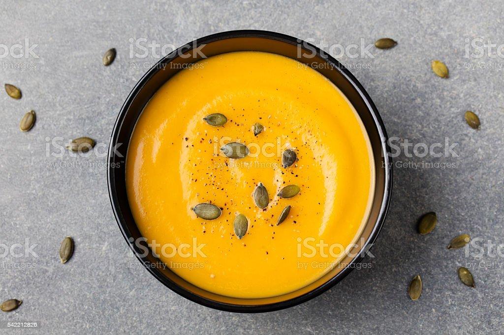 Pumpkin cream soup with pumpkin seeds in a black bowl stock photo