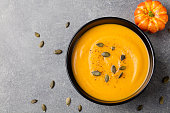 Pumpkin cream soup with seeds in a black bowl.