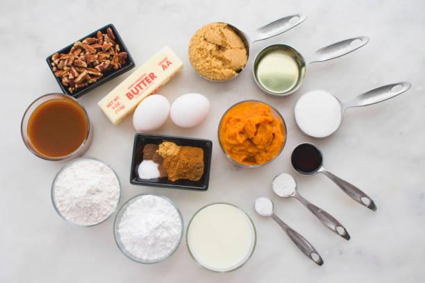 kürbis-cupcakes mit brauner butter zuckerguss zutaten - zimt pekannüsse stock-fotos und bilder