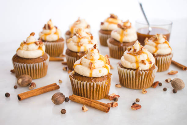 Pumpkin Cupcakes with Brown Butter Frosting Pumpkin cupcakes garnished with pecans and caramel sauce cupcake stock pictures, royalty-free photos & images