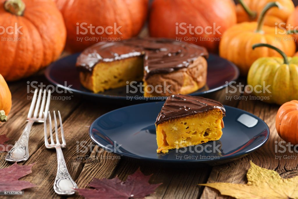 Pumpkin dessert. Delicious pumpkin cake with chocolate icing served with small bright orange pumpkins and marple leaves stock photo