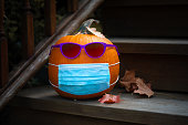 Pumpkin dressed up for Halloween with COVID PPE face mask