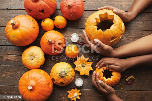 From above view shot of hands holding pumpkin for Hallowing party on dark brown wooden table