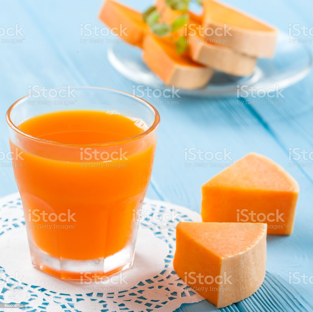 Pumpkin fresh juice in beautiful glasses and jug with pieces of ripe vegetable on white wooden background. Sweet orange juice. Healthy eating, diet theme. Close up photography. Horizontal banner stock photo