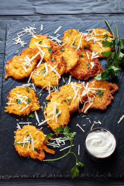Pumpkin fritters on a black stone board, vertical stock photo