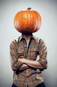 It's Halloween and Thanksgiving season, and pumpkins are on the brain...literally.  A man with a pumpkin on his head, arms folded.