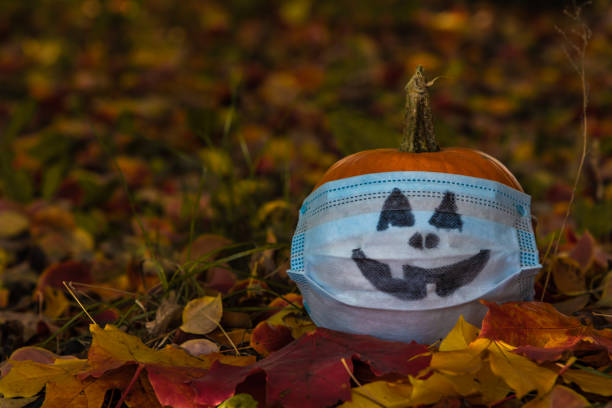 Pumpkin in protective mask on fallen leaves Small orange pumpkin in medical mask with drawn face lies on fallen leaves in autumn park. Selective focus. Theme of Halloween during coronavirus pandemic. Copy space for your text. halloween covid stock pictures, royalty-free photos & images